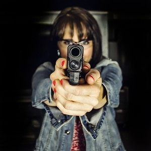 A young woman points a semi-automatic handgun downrange.