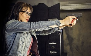 A young woman practices correct form at an Action Target shooting range.